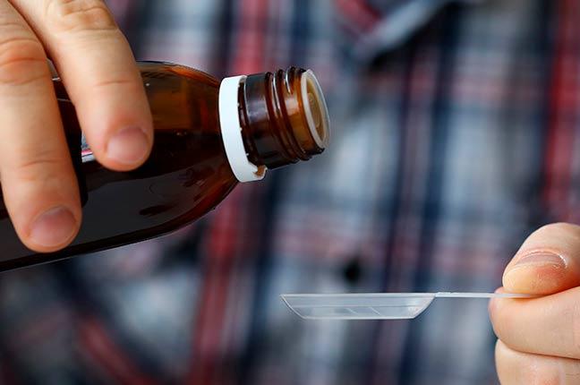 pessoa segurando frasco de remédio
